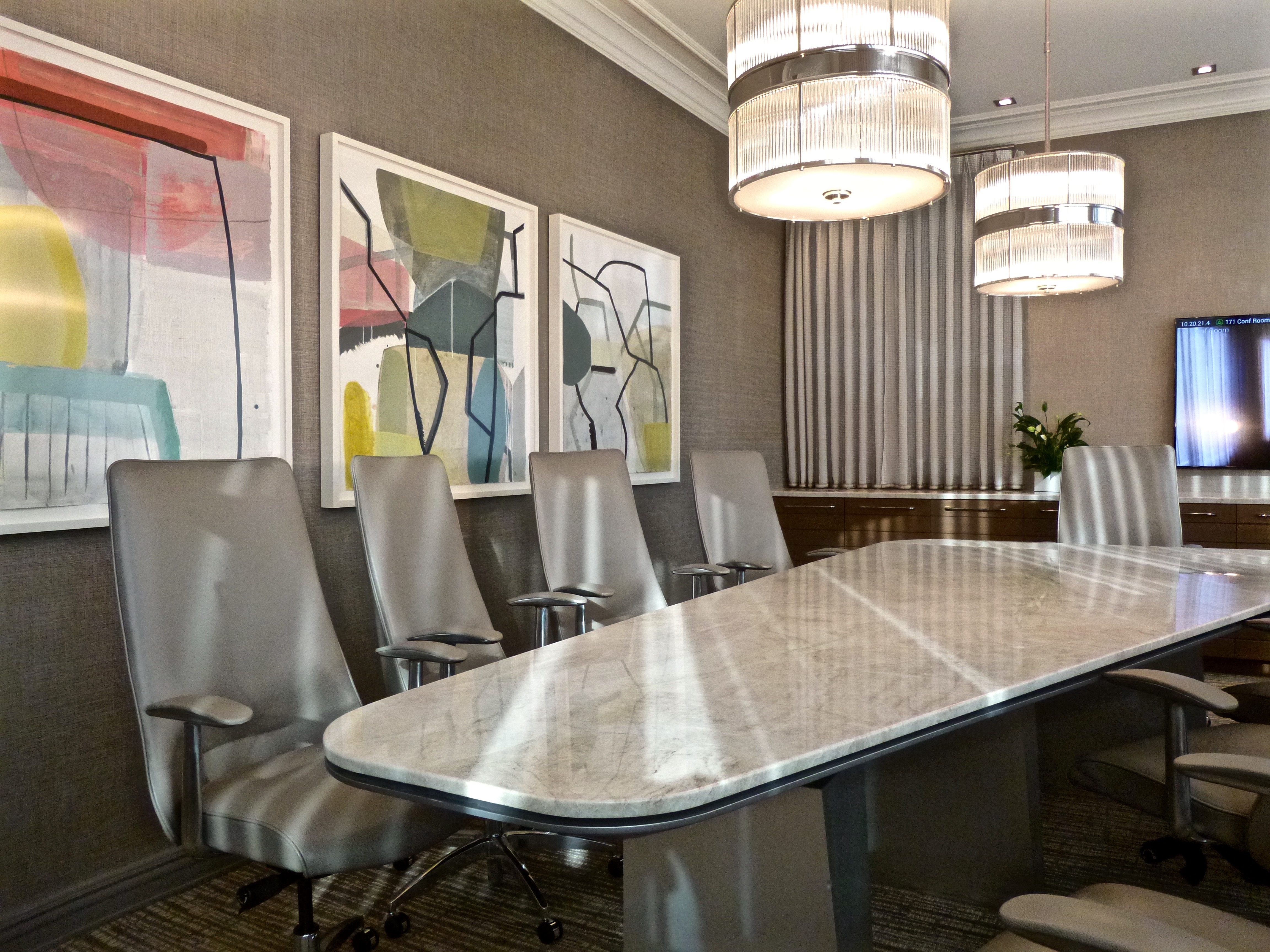 three paintings on paper by artist ky anderson are mounted on the long wall facing the windows modern crystal chandeliers light the conference table